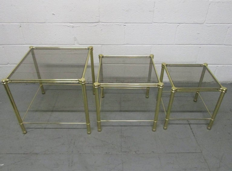 Nesting tables with a decorative brass frame and smoked glass tops. Larger tables measures: 19.25