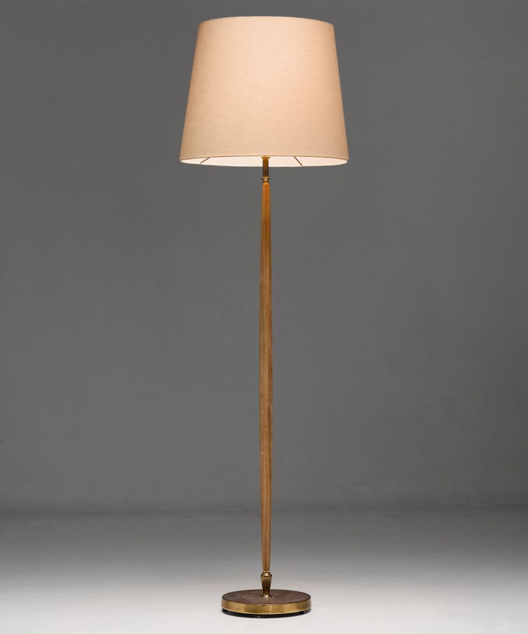 Brass & oak floor lamp  England circa 1950  Elegant floor lamp with oak stand and decorative brass details. On brass base. With new linen shade.