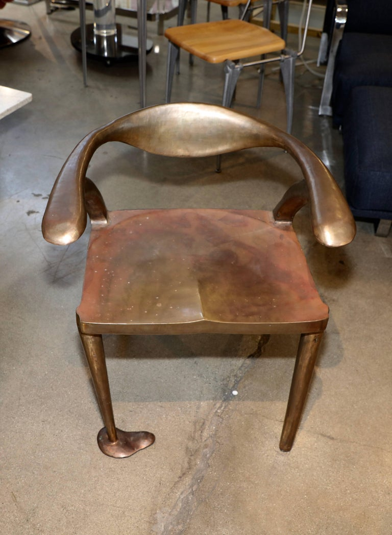 A really unique handmade chair in bronze or brass. It is not signed but is quite wonderfully made. There are seams where the metal has been welded, but the piece its well made and quite comfortable. There are marks and a crack on one leg which does