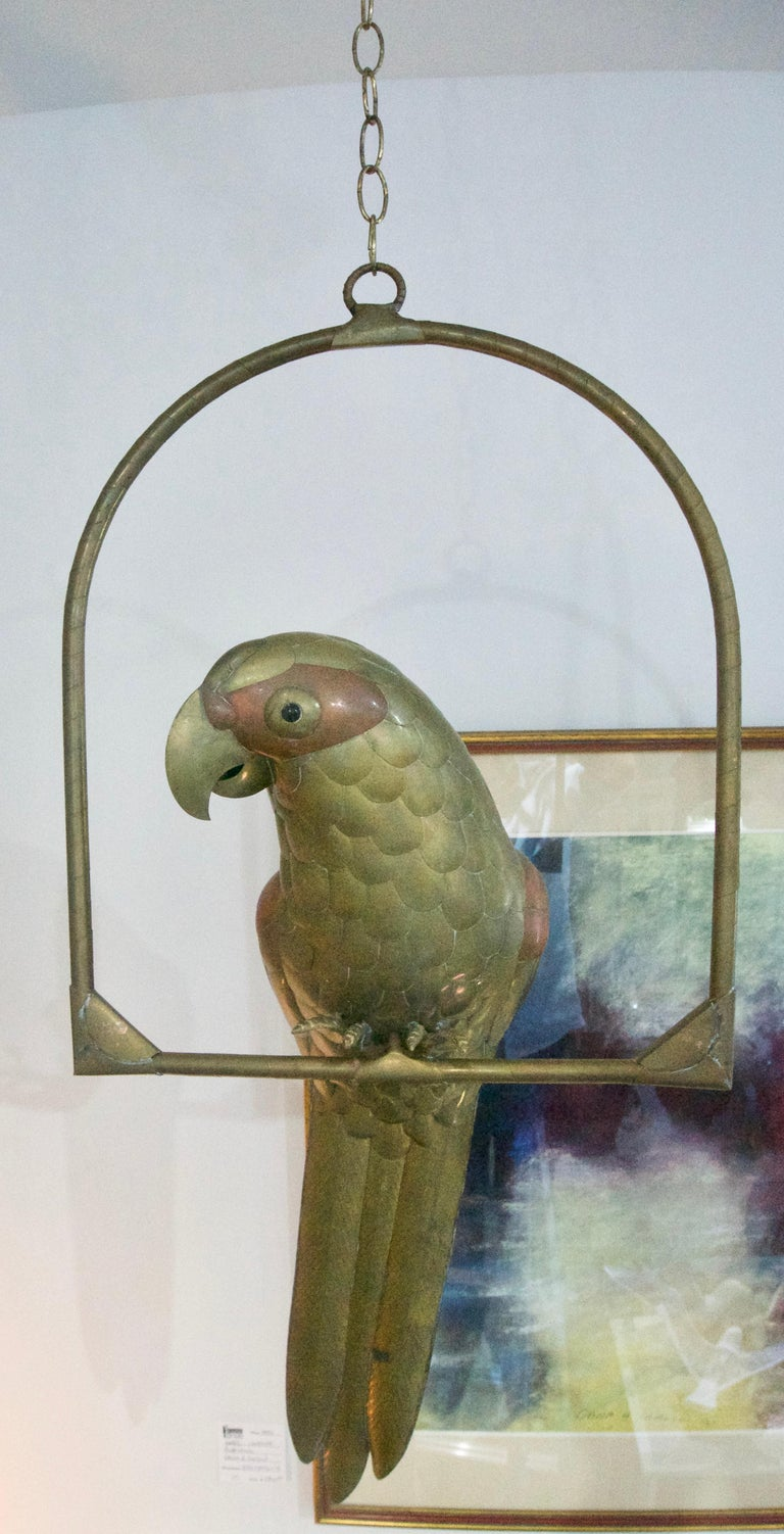 This charming life-size brass and copper Macaw parrot sculpture is by the renowned designer Sergio Bustamante and dates to the 1960s  Dimensions:  From bottom of parrots tail feathers to the top of the round ring is 33