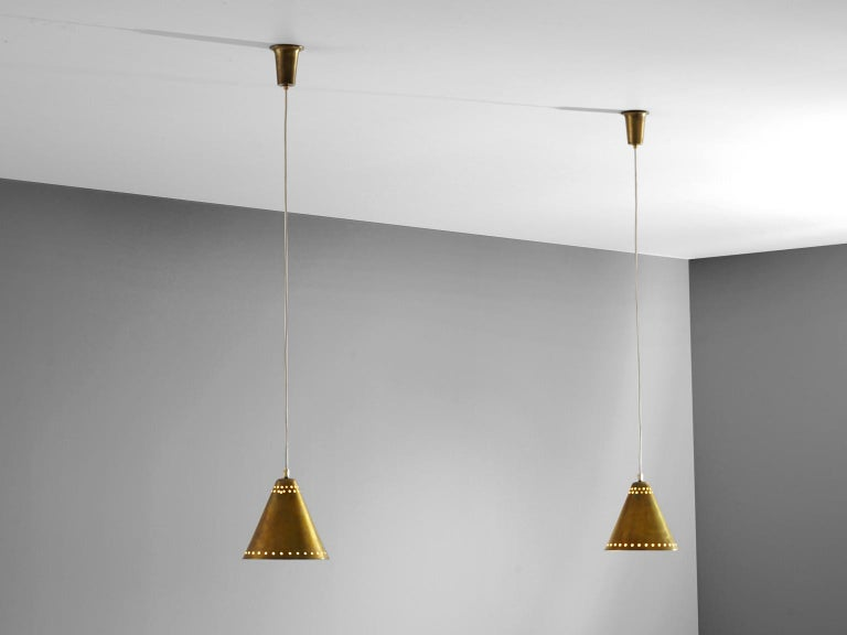 Pendants, brass, Italy, 1950s  Two solid brass pendants in the style of Stilnovo. The shades have a perforated edge on the outer border and are double perforated around the centre of the shade as well. Both pendants come with their original