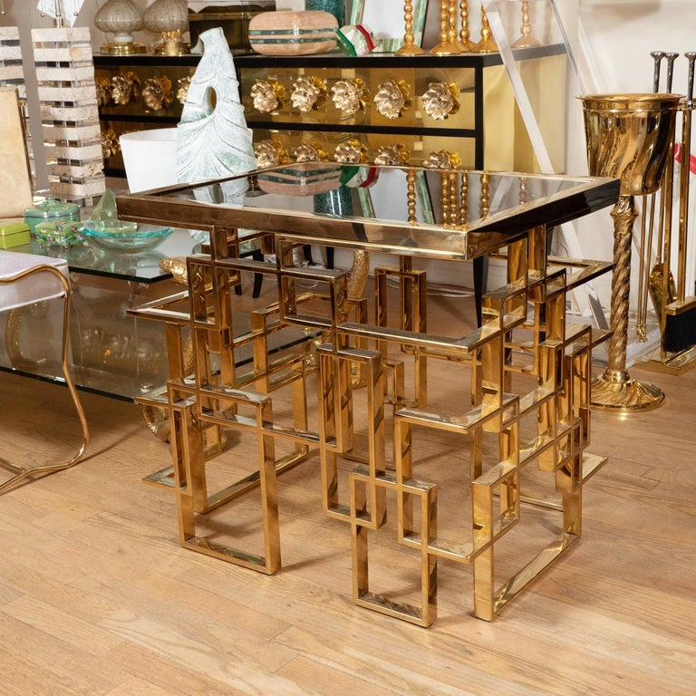 Brass plated metal side table with geometric design base and smoked glass top.