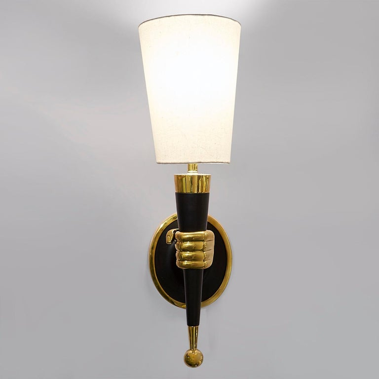 Surrender to the surreal. Available in left or right hands, each sconce is sand cast in brass with blackened accents. The inverted shade completes the torch-like effect. Fab in a dining room or ultra-intriguing in a foyer. The original brass hand