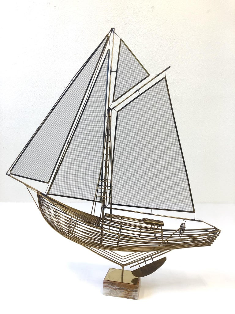 """A beautiful brass sailboat sculpture designed by Curtis Jere in the 1970s. The sculpture sits in a salad onyx base. Dimension: 40"""" wide, 47"""" high, 9"""" deep."""