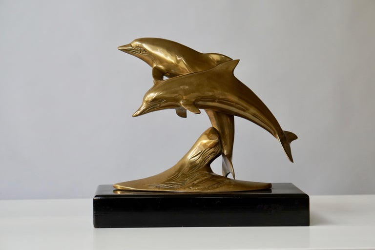 Brass sculpture of dolphins on a wooden base.