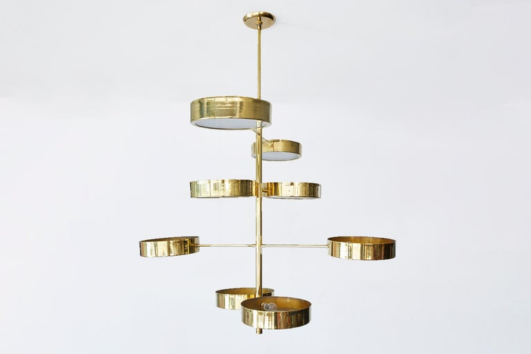 Large brass and glass spiral disc light in the style of Stilnovo. 8 brass discs with milk glass shades on varying length arms. Newly produced in Italy and newly wired to American standards.