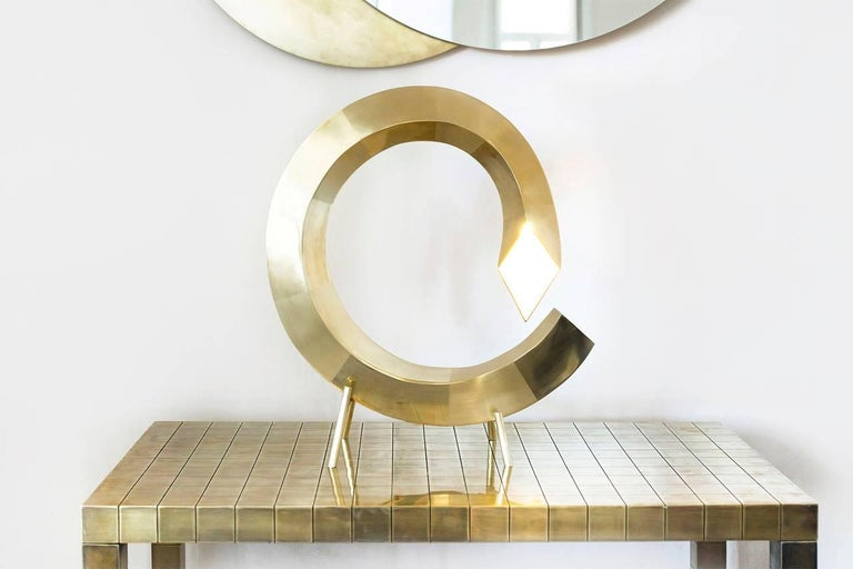 Spiral table lamp, Rooms  Dimensions: 45 x 45 x 12.5 cm Material: Brass, Led   Spiral lamp This lighting object is inspired by the symbolism of its shape – the spiral. Spiral represents the path leading from outer consciousness (materialism,