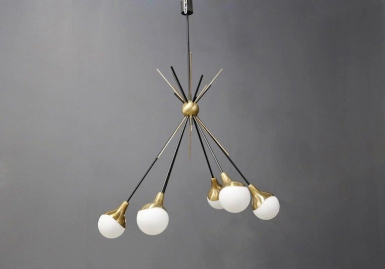 Large Italian midcentury chandelier with six round opaque glass lights, structure in black varnished metal and polished brass with a very light patina. Manufactured in Italy by Stilnovo during the 1950s.
