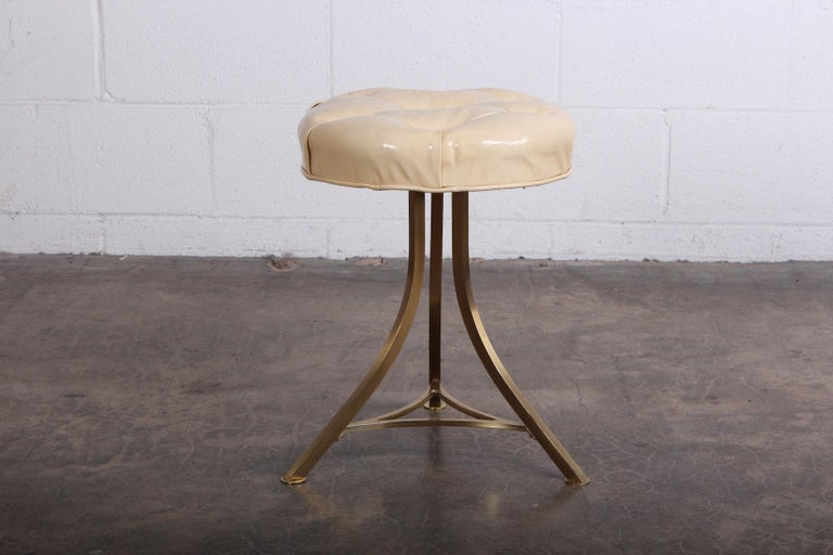 A swiveling brass vanity stool with original leather top. Designed by John Stewart.