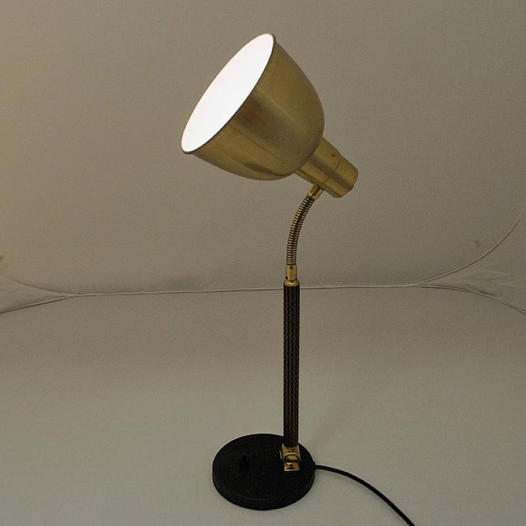 Classic Norwegian brass and metal tablelamp by Selecto AS in the 1950s. Brass shade and body with a black painted metal base. Light switch located on the base. Brass shade and body adjustable back and forth. Stem with a rattan lock. Marked with