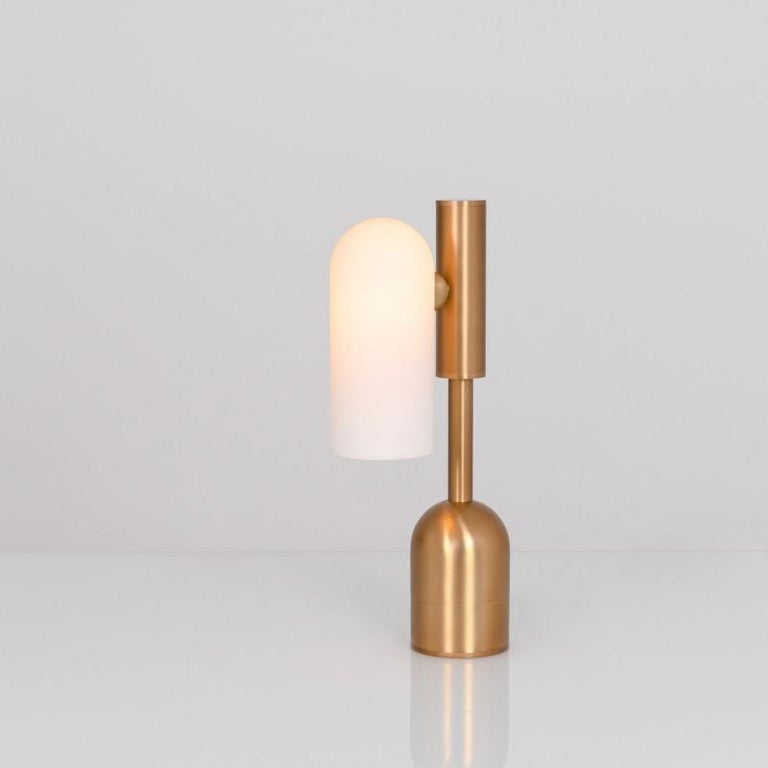Brass table lamp by Schwung Dimensions: W 10 x D 21 x H 44.6 cm Materials: Brass, frosted glass  Finishes available: Black gunmetal, polished nickel, brass Other sizes available   Schwung is a german word, and loosely defined, means energy or