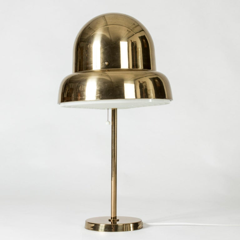 Cool brass table lamp from Bergboms, with an oversized lampshade in a rounded, organic form. A lamella shields the light on the underside.