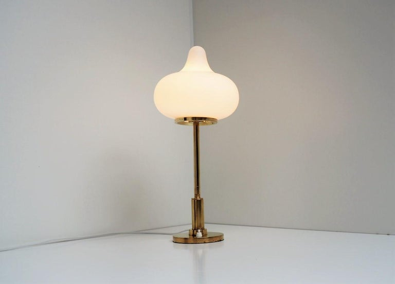 Table lamp made in brass with a beautiful shaped opal glass shade. The lamp is designed by Mogens Hammer and Henning Moldenhawer for Louis Poulsen in 1950s.  It gives a gentle illumination almost like as a lighting sculpture with this adorable