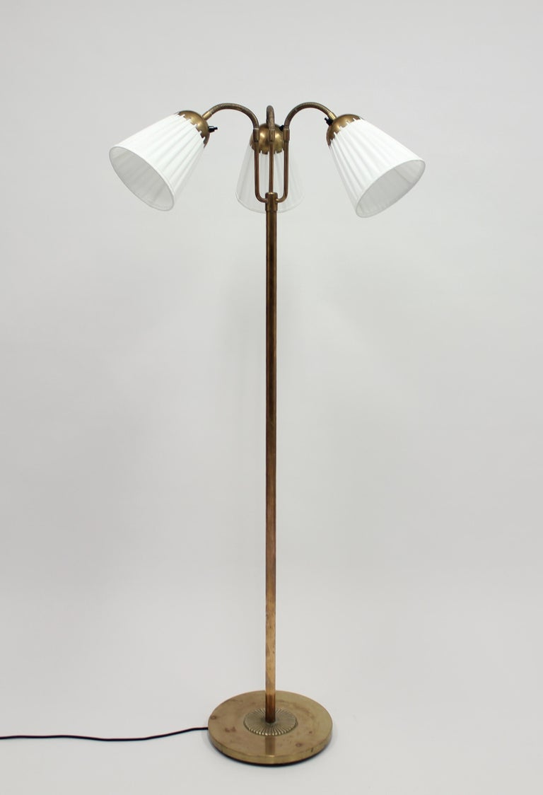 1940s brass three-light floor lamp with pleated shades on so called goose neck arms. Most likely made in Sweden. This is a very good example of the so called