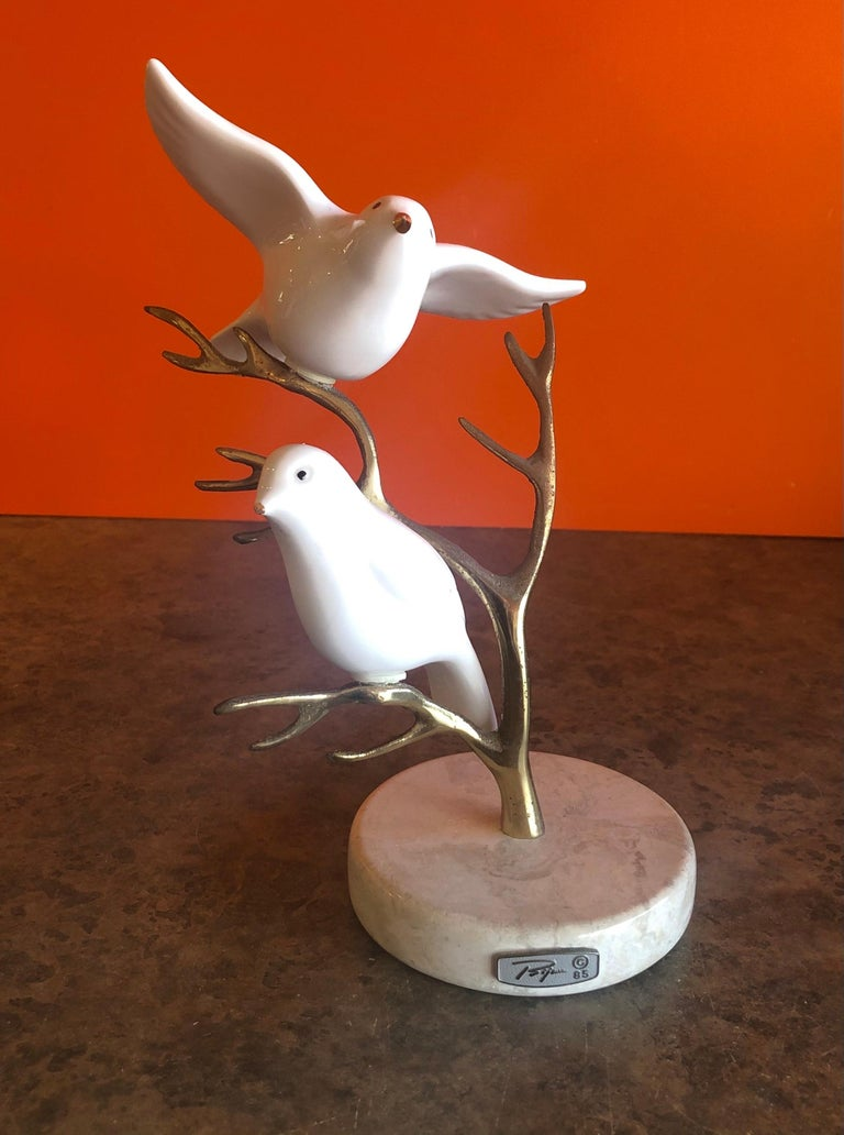Beautiful brass tree with two white ceramic birds table sculpture by Bijan, circa 1985. The patinated tree sits on a 4