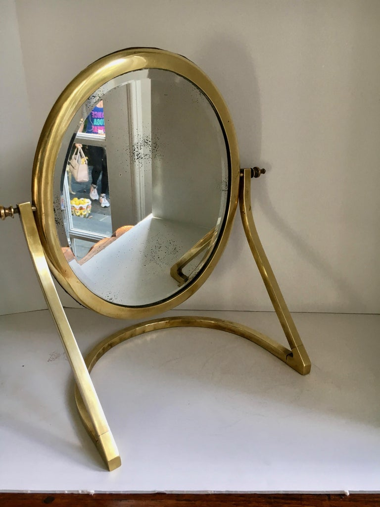A beautiful mirror on unique stand - lovely for a ladies dressing table or handsome as for a man's closet or dressing area. The mirror is beautifully patinated. The brass finials on either side of mirror are wonderful and the rear screw closures are