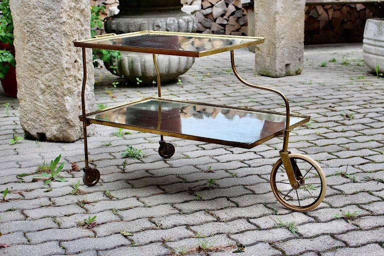 A brass vintage bar cart designed by Josef Frank for Svenskt Tenn circa 1938, Sweden shows two tiers with original mirror glass tops. The bar cart was made of brass, perforated brass, mirror glass and 3 wheels with rubber. The original mirror glass