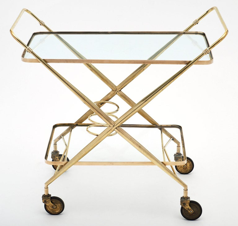 French vintage brass bar cart on casters with two glass shelves and three bottle holders on the bottom shelf. The x-shape of the profile and double-handle feature make this a sleek and functional design solution.