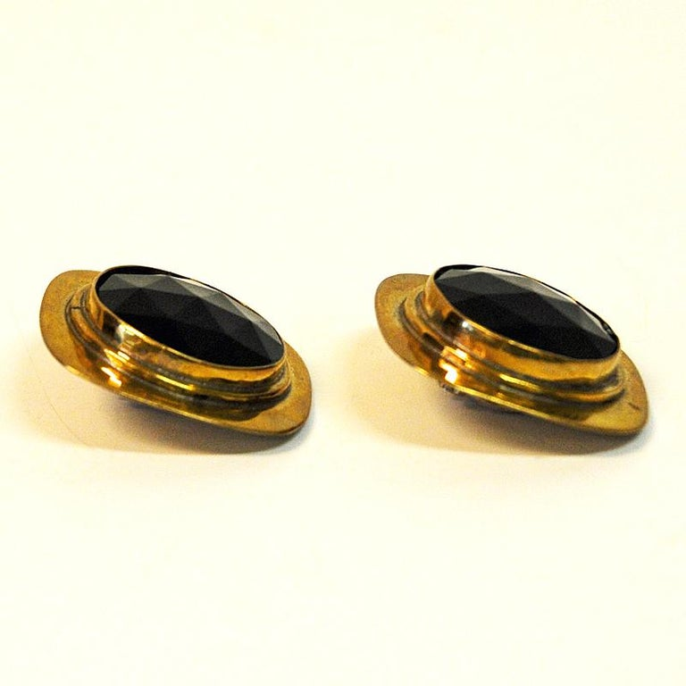 Midcentury brass clip earrings with a dark purple glass stone in the middle with a cut rock shape. Designed by Anna Greta Eker, Norway, 1960s. A typical couple of vintage earrings reflecting some of the best work within design and silversmith art by
