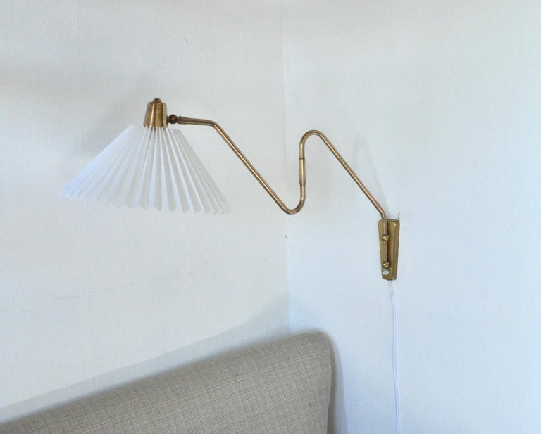 Brass wall lamp with two-piece swing arm. Swivel and wall mount made in brass, mounted with a new pleated screen.  Designed and produced in the 1950s by Norwegian Astra.   Arm length incl. shade: 45 - 83 cm Height: ca. 45 cm  Shade: ca. 9/32.5