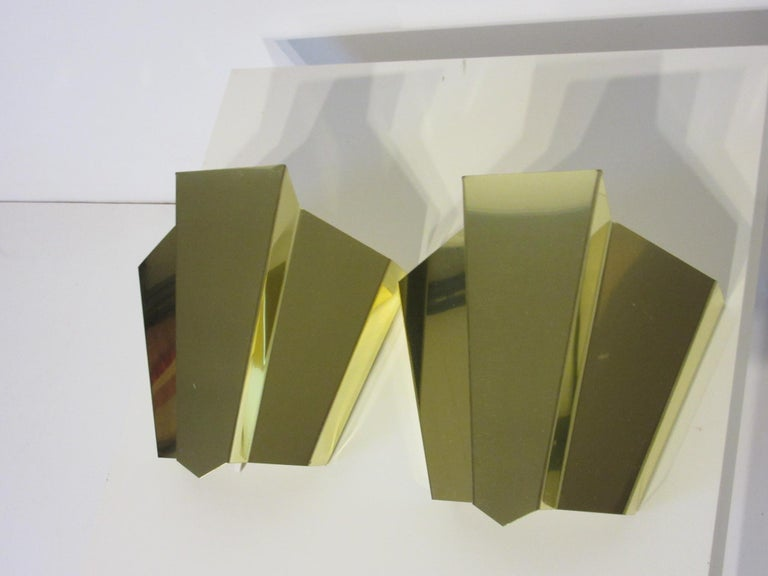 A pair of brass wall scones in the manner of Curtis Jere with internal light fixture with a turn switch socket and electric cord with plug or they can be hard wired.