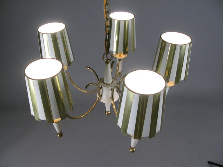 A very charming vintage 1960s five-light chandelier, with a brass frame, and five shades in polished brass and white stripes. Each shade has a mesh diffuser underneath with original wiring.