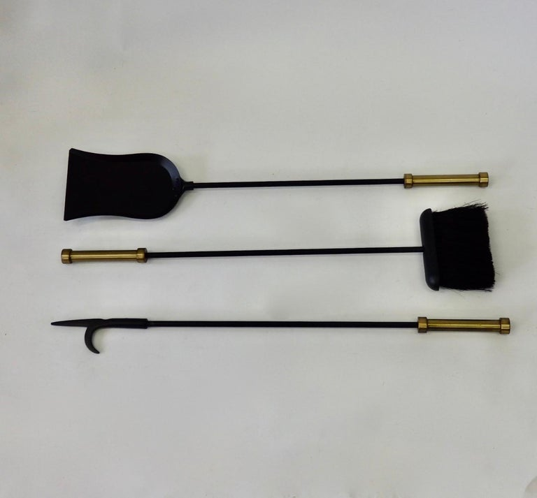Three piece wall hanging fire tool set. Wrought iron tools with brass handles and bracket.