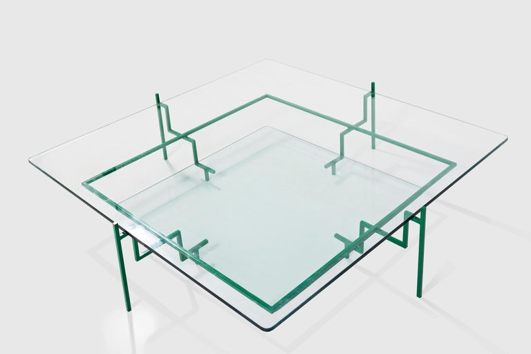 This Brazilian coffee table in solid steel and glass is the fruit of na exercise in geometric minimalismo. Its interdependente elements are indispensable to the stability of the piece, the overlapping glass planes stablish a subtle chromatica