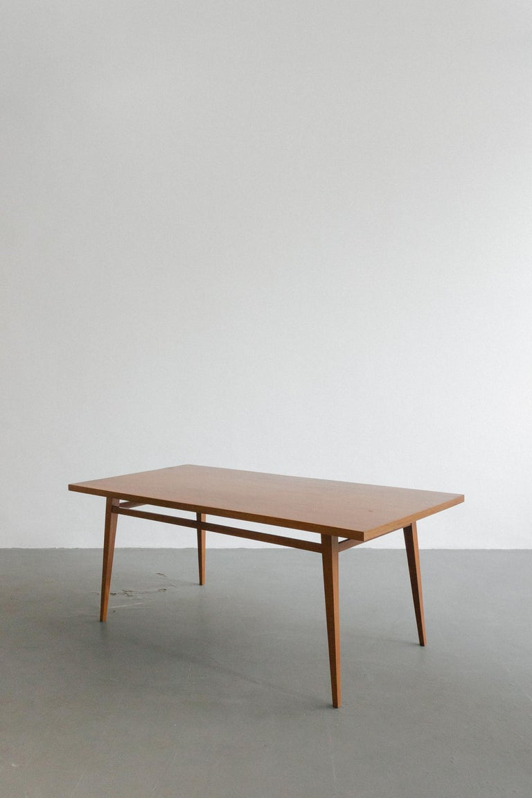 This exquisitely crafted dining table, designed by Joaquim Tenreiro (1906-1992) in 1947, evokes a refined coexistence of traditional values and modern aesthetics. Its delicate shapes give the impression that the pieces float in the