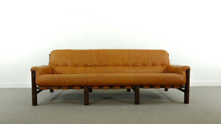 Beautiful lounge sofa Brazilian style from the late 1960s-early 1970s. Cognac colored leather with a beautiful patina. Very elegant and comfortable sofa in good vintage condition. Buttoned leather upholstery mounted by belts and belt buckle to the