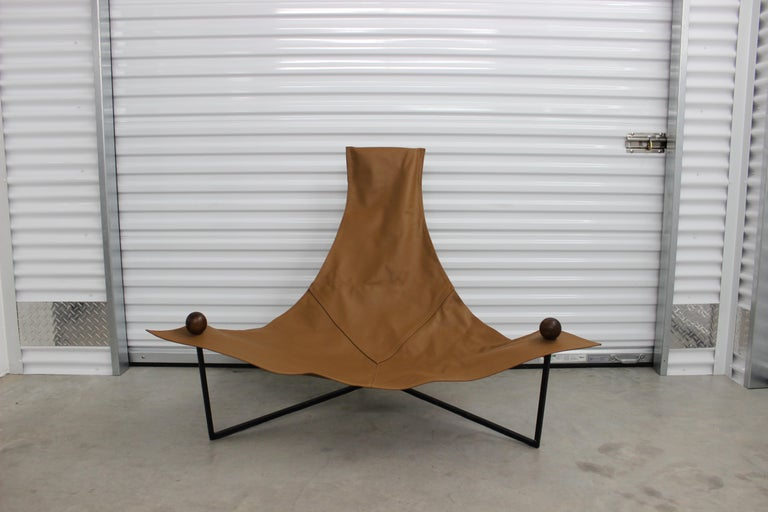 This striking brown 'Poltrona Arraia' armchair was designed by the master of Brazilian modernist design, Jorge Zalszupin. It features 3 legs made of iron, leather seating and Jacaranda wood end caps.  A Brazilian émigré of Polish origin,