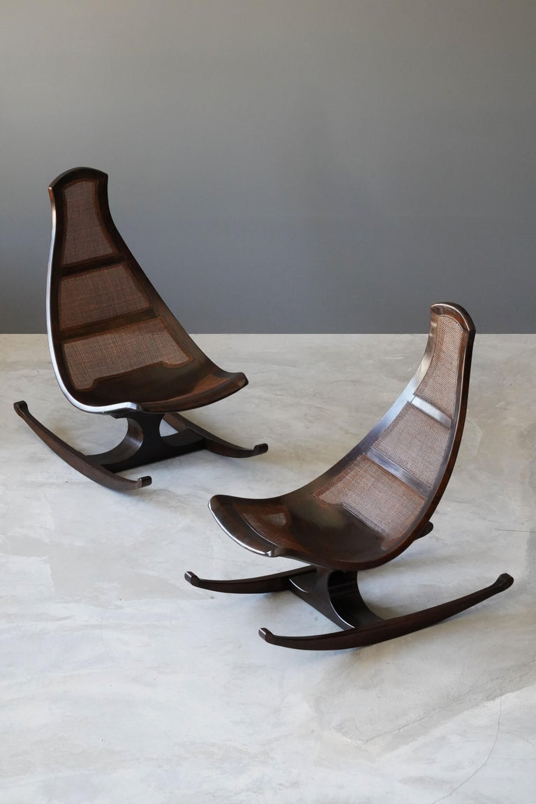 A highly modern and organic rocking lounge chair by an unknown modernist designer. Finely carved mahogany is paired with cane panels. Produced in Brazil, circa 1970s.  Stems from a private collection in Chicago, originally acquired at Marshall