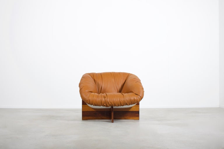 Rare MP-61 chair in very good condition.  Designed by Percival Lafer in the 1970s   This chair has a fiberglass shell which is lacquered white, it is upholstered in a natural brown leather.  The shell is resting on a rosewood cross base.  The chair