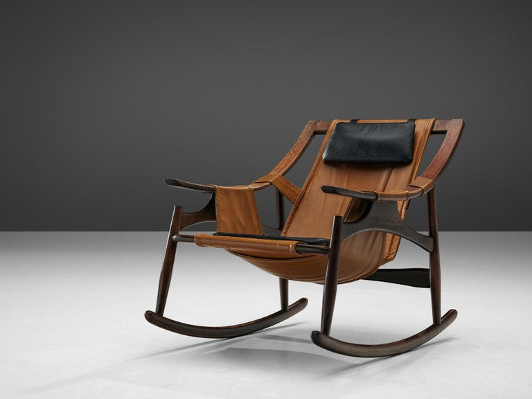 Liceu de Artes e Oficios, rocking chair, darkened wood and leather, Brazil, 1960s.   Beautiful rocking lounge chair in dark walnut with a brown suede upholstery. The frame has the appearance of a wooden skeleton. An open character with beautiful