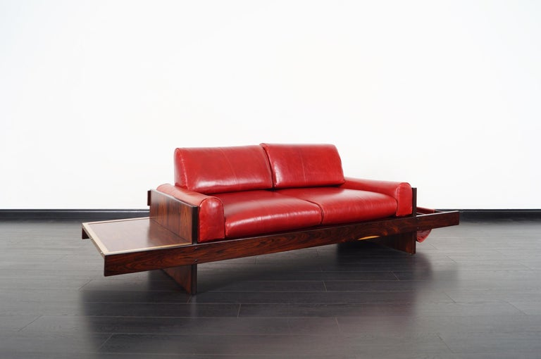 Incredibly unique vintage Brazilian rosewood and leather sofa attributed to Celina Moveis. Features an attached floating side table and magazine holder.