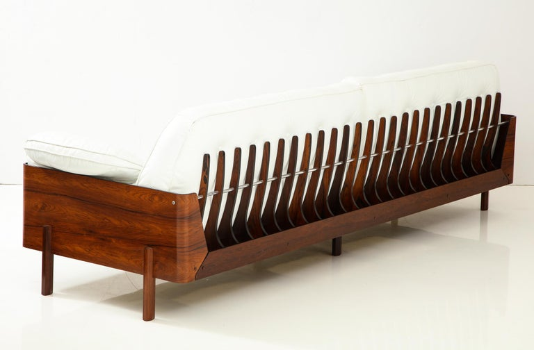 Eight foot long sofa in beautifully figured Jacaranda wood with a series of skeletal fins along the back connected with an aluminum rod, and original white leather cushions. A visually impressive design made in Sao Paulo, Brazil, circa 1965. A rare