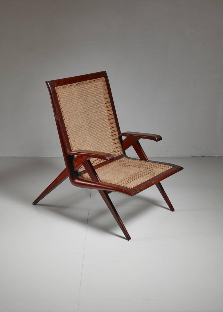 A Brazilian wooden armchair with a seating and backrest of woven cane. Beautiful lining.  The seat is in a wonderful condition and is excellent for reading or active relaxation.