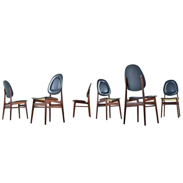 These solid walnut dining chairs by Sørheim are a beautiful example of Classic Norwegian design. The interesting raised edges on the cushions and high backs provide both comfort and character. Don't let these dainty chairs fool you, the elegant