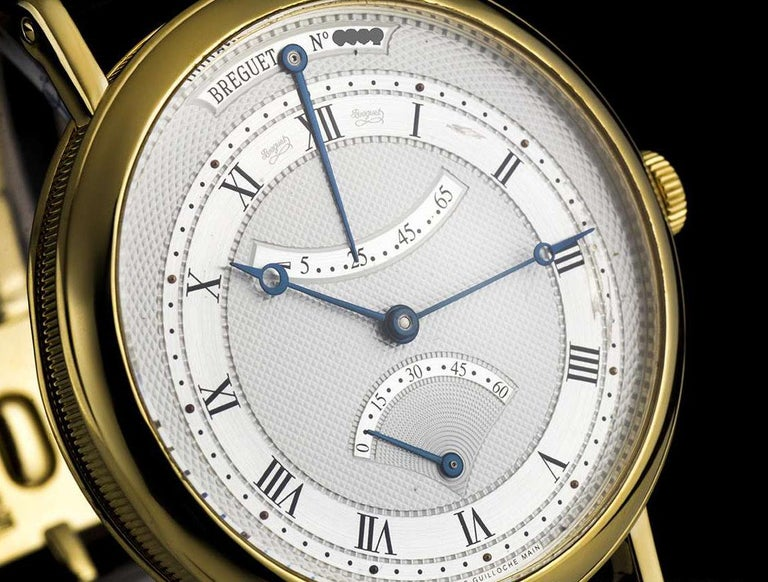 An 18k Yellow Gold Classique Gents Wristwatch, silvered gold dial hand engraved on a rose engine, an off-centred chapter ring with roman numerals, retrograde seconds at 6 0'clock, power reserve indicator at 12 0'clock, an 18k yellow gold fixed