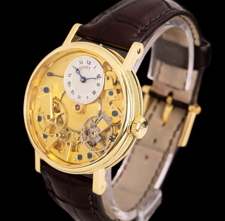 An 18k Yellow Gold Tradition Gents Wristwatch, champagne open worked dial with an off-centred silver guilloche dial hand engraved on a rose engine with roman numerals, power reserve indicator between 9 and 11 0'clock, blued steel Breguet open-tipped
