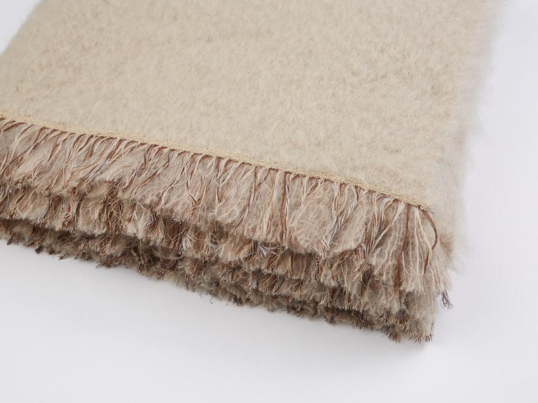 Brewster, a chique beige throw blanket made of the finest New Zealand mohair. Characterized with a hand embroidered fringe border completely embroidered by hand.  Based in the Netherlands and India's Uttar Pradesh, Jupe by Jackie is an