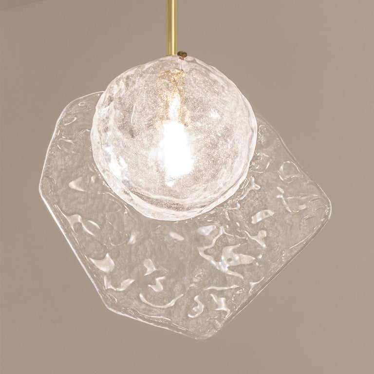 Inspired by the breeze of the venetian lagoon, the Brezza pendant by form A, is constructed from hand blown Murano glass with a bubble infused core and a textured fin. Shown on a polished brass stem.