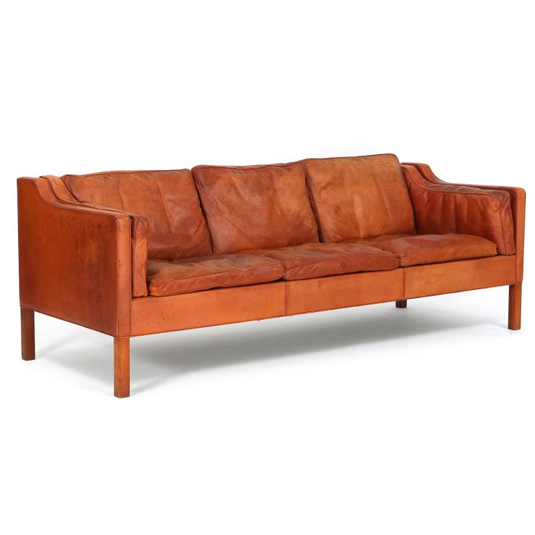 A freestanding rectangular three seater sofa with nutwood square legs.  The sides, back and cushions upholstered with patinated natural leather.  Model 2213. Designed 1963. Manufactured and marked by Fredericia