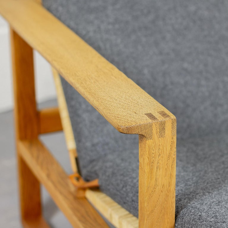 An early BM-2254 'Slædestolen' or Sled chair with foot stool designed by Børge Mogensen for Fredericia Stolefabrik, Denmark, 1950s. Fully restored with new cane seat & back and new upholstery in Moon Spectrum 100% pure wool. Solid oak frame. Brass