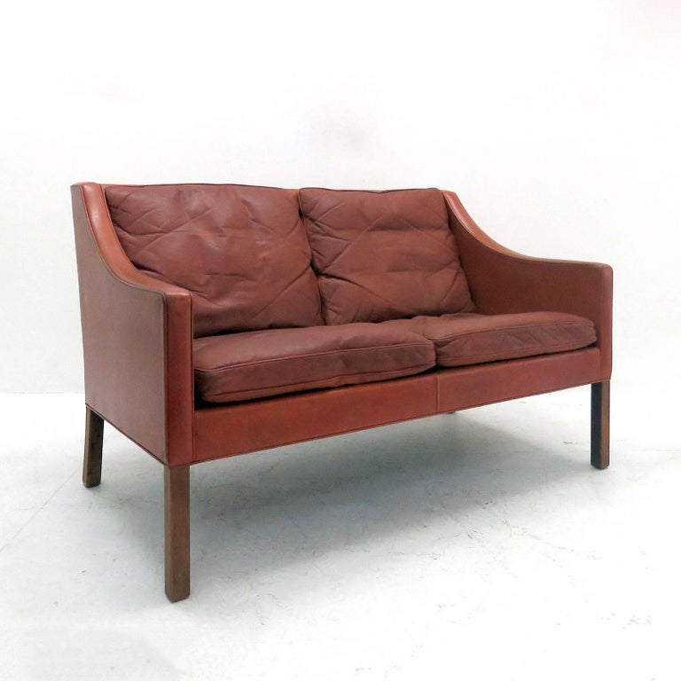 Stunning two-seat sofa model no. 2208, designed by Børge Mogensen in 1963 and produced by Frederica Stolefabrik, Denmark, in red cognac colored leather on mahogany legs with loose down cushions.