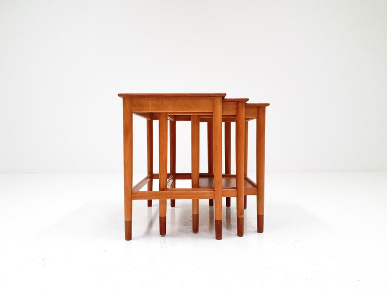 A set of nesting tables by Børge Mogensen. Manufactured by Søborg Møbelfabrik in Denmark, 1960s.  Made from both teak and beech, with teak tabletops and feet and beech frames the contrast in woods offers a very attractive contrast.  The timeless