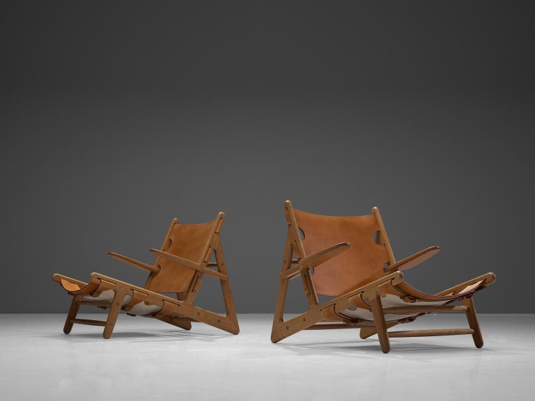 Børge Mogensen for Fredericia Stolefabrik, hunting chairs, oak and cognac saddle leather, Denmark 1950.   The hunting chair was Mogensens first work with a solid wooden frame and saddle leather seating. This iconic piece was the first in a line of