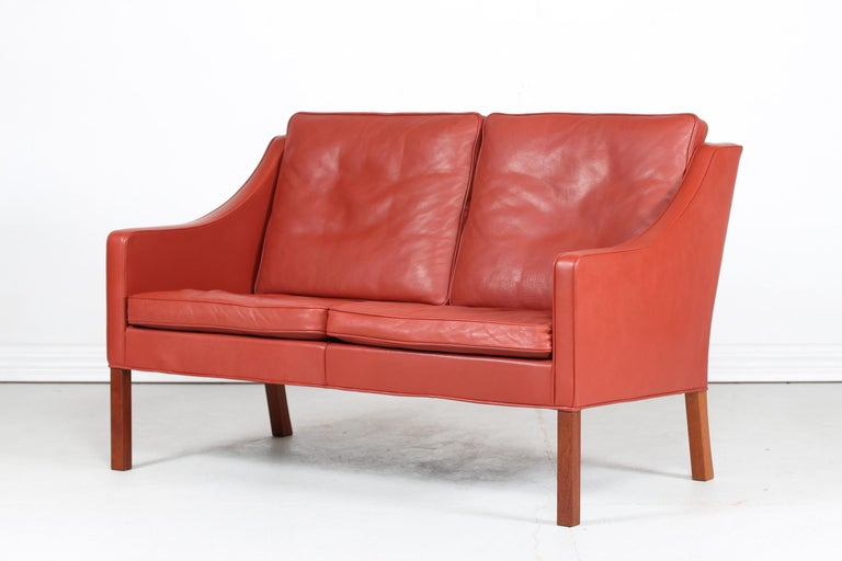 Danish vintage Børge Mogensen sofa for 2 persons model 2208. It's upholstered with original brick red / red brown leather. The legs are made of mahogany.  The cushions are filled inside with granules and natural feathers which gives the sofa a very