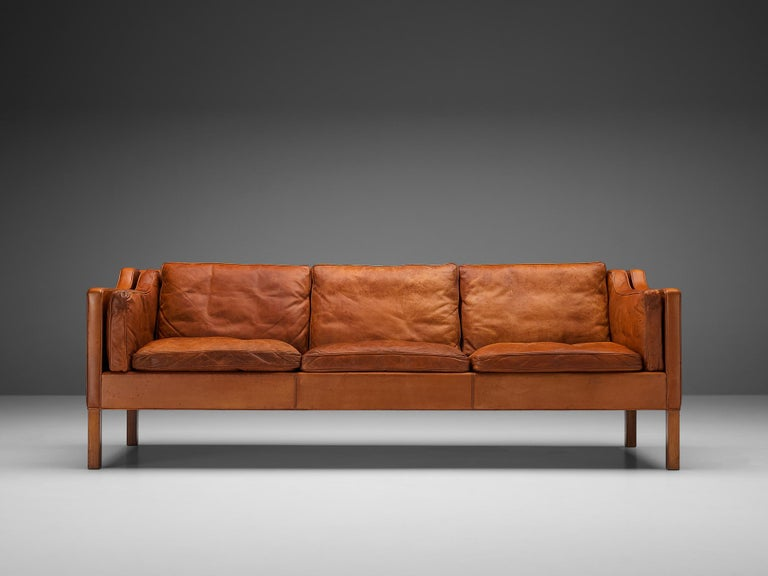 Børge Mogensen for Fredericia Stolefabrik, three-seat sofa model BM2213, leather and stained oak, Denmark, 1962  Very well balanced design by Børge Mogensen. The model 2213 was designed by Mogensen for his own home. The cognac leather shows