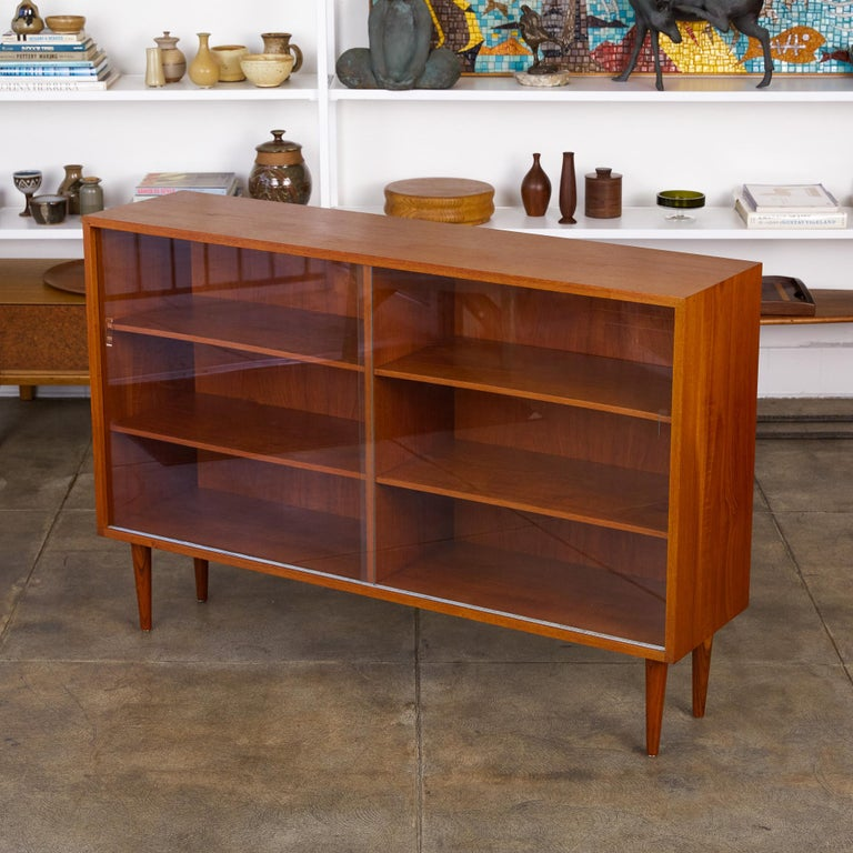 """Børge Mogensen teak bookcase for Aalborg, Denmark, circa 1950s. The cabinet features a slender teak exterior frame and tapered turned legs. It has glass sliding door openings and four adjustable shelves.  Dimensions: 54.25"""" width x 13.5"""" depth x"""